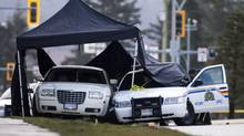 An RCMP officer looks over the scene of a deadly police shooting in Surrey, B.C., on March 3, 2011. (Rafal Gerszak for The Globe and Mail)