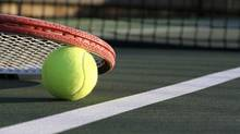 Tennis Ball & Racket on a Green Outdoor Court (David Lee/Getty Images/iStockphoto)