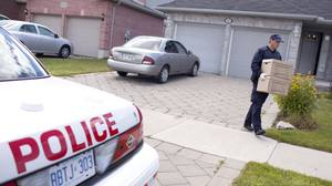 RCMP investigators remove evidence from a home in London, Ontario August 26, 2010 where they arrested a man in a terrorism-related investigation.