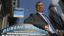 Director Sakthi Ariaratnam poses outside a branch of Thomas Exchange Global foreign exchange in the City of London July 1, 2014. (LUKE MACGREGOR/REUTERS)