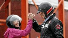 Conservative leader and Canada's Prime Minister Stephen Harper high-fives his wife Laureen after riding all-terrain vehicles during a campaign stop at a farm in Wainfleet, Ontario (CHRIS WATTIE/CHRIS WATTIE/REUTERS)