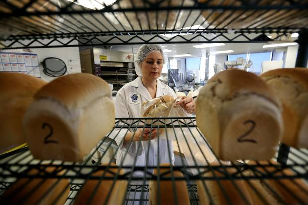 Yulia Borsuk, a technical specialist in baking technology at the Canadian International Grains Institute lab, packages bread made from pulse flour at the company's research lab in Winnipeg.