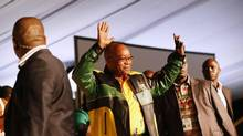 Flanked by security officials, President Jacob Zuma waves upon arrival at the start of the 53rd National Conference of his ruling African National Congress (ANC) in Bloemfontein December 16, 2012. (MIKE HUTCHINGS/REUTERS)