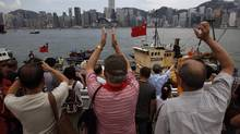 Supporters applaud as Hong Kong fishing vessel Kai Fung No. 2, which went to the islands disputed by China and Japan, docks at Hong Kong's Victoria Harbour on Aug. 22. (BOBBY YIP/Reuters)