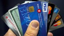 Credit cards are displayed in Montreal on December 12, 2012. A new survey by Statscan says Canadian families are worth more now but they also owe more. (Ryan Remiorz/THE CANADIAN PRESS)