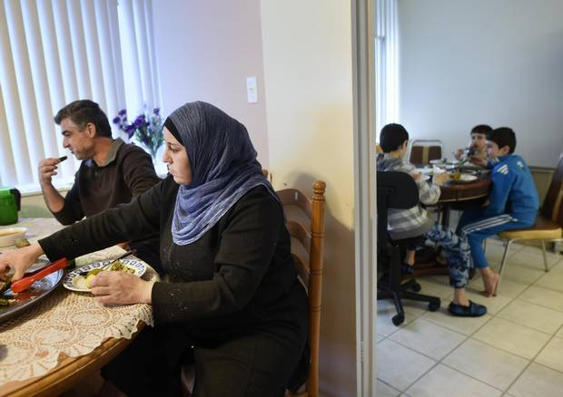 Ahmad Alhaj Ali and his wife Manal Alumoor eat in one room while their three sons eat in the kitchen.