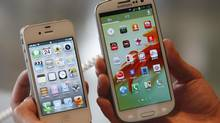 An employee holds Apple's iPhone 4S, left, and Samsung's Galaxy S III at a store in Seoul on Friday. Samsung Electronics has not violated the iPhone design, a Seoul court has ruled. (LEE JAE-WON/REUTERS)