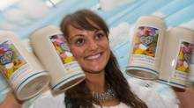 Model Julia presents the new beer mugs for 2014 at the Oktoberfest beer festival grounds in Munich, Germany, Thursday Aug. 21, 2014. Oktoberfest takes place from Sept. 20 to Oct 5, 2014. (Peter Kneffel/AP)