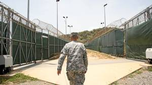 Andrew McManus, deputy commander of Guantanamo's detention operations, walks between barbed-wire-topped fences in the base's Camp VI, copied after a U.S. county prison.