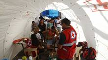 Residents, whose homes were destroyed by Typhoon Haiyan, receive medical aid from the Philippine Red Cross outside their temporary shelters in Tacloban city in central Philippines November 16, 2013. (EDGAR SU/REUTERS)