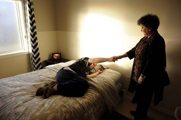 Holding his sister's hand, Scott lies down in bed at his room in Moose Jaw, his first new home in decades.