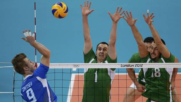 Italy's Ivan Zaytsev (L) spikes the ball against Bulgaria's Georgi Bratoev and Nikolay Nikolov (R) during their men's bronze medal volleyball match at Earls Court during the London 2012 Olympic Games August 12, 2012. (OLIVIA HARRIS/REUTERS)