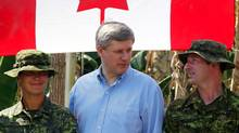 Prime Minister Stephen Harper, centre, talks with members of the Canadian Armed Forces running a Canadian water purification site in the earthquake stricken town of Jacmel, Haiti on Feb. 16, 2010. (FRED CHARTRAND/THE CANADIAN PRESS)