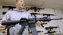Chicago gun stores would have to videotape purchases under an ordinance approved by the Chicago City Council on June 25, 2014. Here John Jackson, co-owner of Capitol City Arms Supply, shows off an AR-15 assault rifle for sale in 2013 (Seth Perlman/AP)