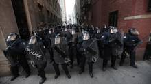 Police officers wearing riot gear fill an alley during a protest ahead of the G20 Summit in downtown Toronto June 25, 2010. (MARK BLINCH/REUTERS)
