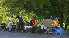 A cluster of homeless people gather on the side of a road near a treed area where Abbotsford city officials spread a load of chicken manure in an effort to keep them from living and sleeping in a camp in Abbotsford, B.C., on June 6, 2013. (Jeff Vinnick for The Globe and Mail)