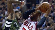 Chicago Bulls' C.J. Watson drives to the net past Toronto Raptors' Amir Johnosn during first half NBA play in Toronto on Wednesday. (Pawel Dwulit/The Canadian Press)