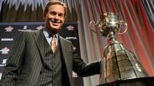 CFL commissioner Mark Cohon poses with the Grey Cup at the Commissioner's State-of-the-League Address in Toronto on Friday, November 23, 2012. (The Canadian Press)