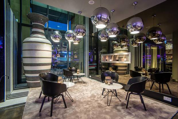 A modern fireplace illuminates one of several convivial gathering spots in the lobby of the G&V Royal Mile Hotel Edinburgh.