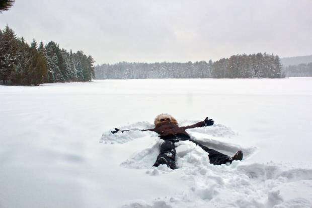 A camper makes snow angels by the banks of Mew Lake.