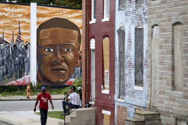 A mural depicting Freddie Gray is seen past blighted row homes in Baltimore on June 23, 2016, at the intersection where Mr. Gray was arrested.