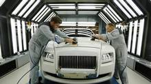 Employees give a Rolls Royce Ghost its final finish polish at the Rolls Royce Motor Cars factory near Chichester, southern England, April 24, 2013. Britain's economy dodged a return to recession and grew faster than expected in the first three months of this year. (LUKE MACGREGOR/REUTERS)