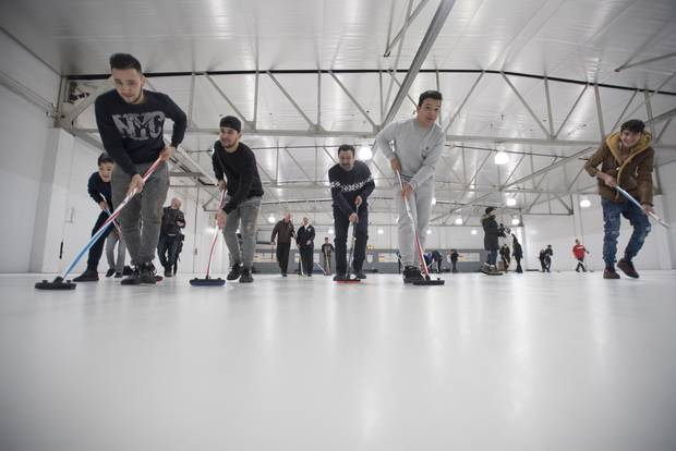 Refugees are photographed during a day trip to the Royal Canadian Curling Club where they had their first curling experience, on March 15, 2017.