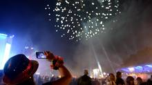 Fireworks illuminate the sky as German fans celebrate their team after Germany won against Argentina by 1-0 at the soccer World Cup final in Rio de Janeiro, Brazil, at a public viewing area called 'Fan Mile' in Berlin, Sunday, July 13, 2014. (Britta Pedersen/AP)