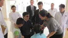 In this photo released by the U.S. embassy Beijing Press Office, blind lawyer Chen Guangcheng, in wheel chair, meets his wife Yuan Weijing, right, daughter Chen Kesi, in blue shirt at second right, and son Chen Kerui, left, at a hospital in Beijing, Wednesday, May 2, 2012. (ASSOCIATED PRESS/ASSOCIATED PRESS)