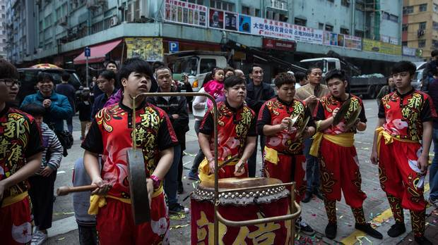 People watch as a lion dance team performs on a street during Lunar New Year celebrations in Hong Kong on February 12, 2016.