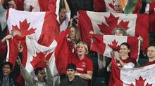 Canadian fans wave the flag during the London 2012 Olympic Games men's field hockey qualifying match between India and Canada in New Delhi, Feb. 22, 2012. (B MATHUR/REUTERS)