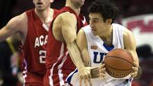 UBC Thunderbird's Alex Murphy, right, heads past Acadia Axemen Justin Boutlier, left, and Tyler Lutton in CIS Final 8 men's basketball action in Halifax on Friday. (Andrew Vaughan/The Canadian Press)