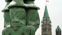 The Three Watchmen, by Haida artist James Hart, keep vigil over the Parliament Buildings in Ottawa. (Sean Kilpatrick/Sean Kilpatrick/THE CANADIAN PRESS)