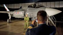 A Canadian Forces pilot has his picture taken in front of a F-35 Joint Strike Fighter model prior to a procurement announcement in Ottawa on July 16, 2010. (Adrian Wyld/THE CANADIAN PRESS)
