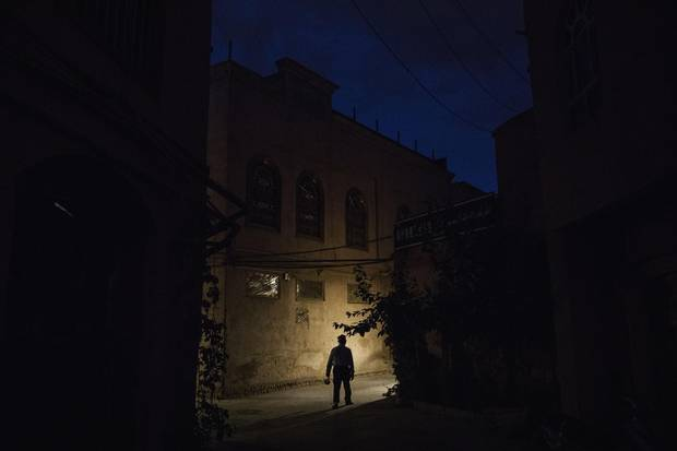 An ethnic Uyghur man walks in an alleyway near a local police station in the old town of Kashgar, in the far western Xinjiang province, China on June 27, 2017.