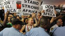 Environmental activists storm the plenary session at United Nations climate-change talks in Durban, South Africa on Dec. 9, 2011. (MIKE HUTCHINGS/REUTERS)