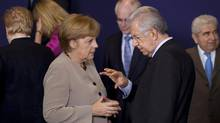 German Chancellor Angela Merkel, left shares a word with Italian Prime Minister Mario Monti during a group photo at an EU Summit in Brussels on Thursday, June 28, 2012. (Michel Euler/AP)