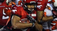 Calgary Stampeders' Jon Cornish, grimaces as he collides with other players during second half CFL football action against the B.C. Lions in Calgary, Alta., Friday, June 28, 2013. (Jeff McIntosh/The Canadian Press)