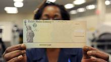 A U.S. Treasury Department employee holds a blank U.S. Treasury cheque before it's run through a printer in Philadelphia. (William Thomas Cain/Getty Images)