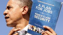 U.S. President Barack Obama holds up his plan for jobs during a campaign rally in Delray, Florida October 23, 2012. (KEVIN LAMARQUE/REUTERS)
