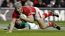 Wales' Jonathan Davies goes over for a try against Ireland during the Six Nations rugby match at Aviva stadium in Dublin on Sunday. (CATHAL MCNAUGHTON)