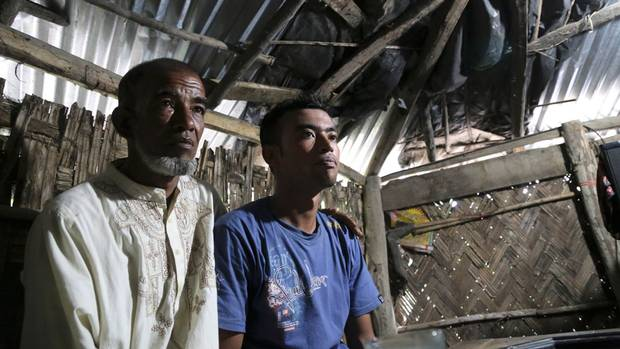 Abul Taher sits with his son Muhammad Selim, who left Bangladesh earlier this year as part of a tide of people seeking better prospects in Malaysia.