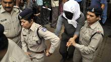 Police escort a Swiss woman, centre, for a medical examination at a hospital in Gwalior, in the central Indian state of Madhya Pradesh, March 16, 2013. (AP)