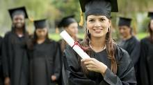 Female graduate outdoors with a group behind her (iStockphoto)