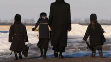 Male member of the Lev Tahor ultra-orthodox Jewish sect walks children home from school in Chatham, Ont. Monday, Feb. 3, 2014. (Dave Chidley/THE CANADIAN PRESS)
