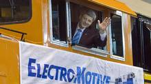 Prime Minister Stephen Harper waves from the cabin of an engine at Electro-Motive Diesel in London, Ont., on March 19, 2008. (Frank Gunn/Frank Gunn/The Canadian Press)