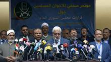 """Egyptian Secretary General of Muslim brotherhood Mahmoud Hussein, center, reads a statement in front of a banner that reads in Arabic """"A press conference for the Muslim brotherhood about the decisions of the general Shura council"""" during a press conference in the Muslim brotherhood headquarters in Cairo, Egypt, April 30, 2011. The once outlawed Muslim Brotherhood says it will contest half of the seats in Egypt's parliamentary elections in September, revealing plans to become a major force in the country's post-revolution politics. (Khalil Hamra/AP/Khalil Hamra/AP)"""