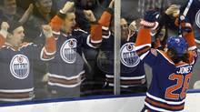 Edmonton Oilers' Ryan Jones (R) celebrates his goal against the Chicago Blackhawks with fans during the first period of their NHL hockey game in Edmonton November 19, 2011. The Oilers won 9-2. REUTERS/Dan Riedlhuber (Dan Riedlhuber/Reuters)