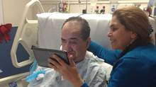 Parichehr Salasel shows her husband Hassan Rasouli family photos on a tablet on friday oct 18, 2013 after news that the Supreme Court of Canada has dismissed an appeal that would have permitted doctors to end life support for her husband. (Mojgan Rasouli/Globe and Mail)