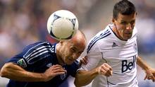Sporting Kansas City's Aurelien Collin, left, of France, heads the ball and checks Vancouver Whitecaps' Sebastien Le Toux, of France, into the sideline boards during first half MLS soccer game action in Vancouver, B.C., on Wednesday April 18, 2012. THE CANADIAN PRESS/Darryl Dyck (Darryl Dyck/CP)